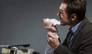 Inspired author biting crumpled paper