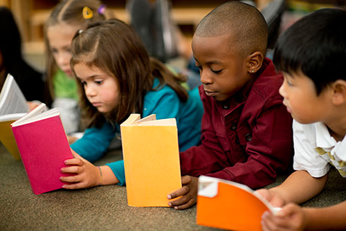Children with average and lower vocabularies reading e-books learn more with an adult reader than pre-recorded voice