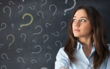 Thinking business woman in front of question marks drawn on blackboard