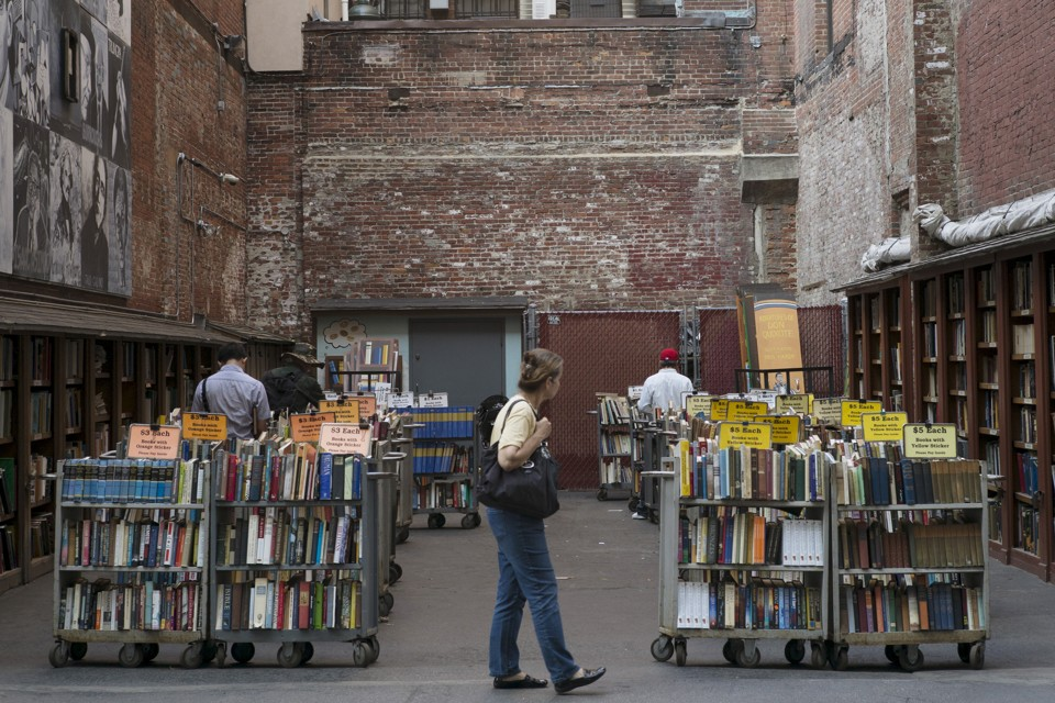 Customers browse the used books for sale from the Brattle Book Shop in an alley in downtown Boston